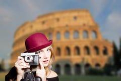 Ragazza in vetri dei pantaloni a vita bassa che tengono macchina fotografica sul Colosseo Immagine Stock Libera da Diritti