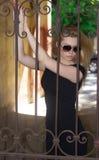 Ragazza in vetri ed in un vestito nero sulla via Fotografia Stock