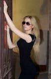 Ragazza in vetri ed in un vestito nero sulla via Immagine Stock