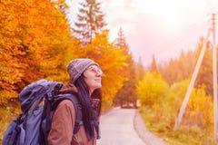 Ragazza in vetri rossi con lo zaino in autunno fotografia stock