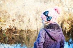 Ragazza vicino ad acqua nella stagione fredda Vista posteriore immagini stock