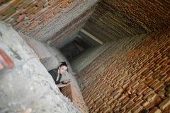 Ragazza vicino al muro di mattoni nello stile militare immagine stock libera da diritti