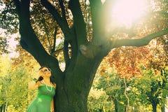 Ragazza vicino all'albero con il chiarore del sole Fotografia Stock