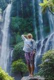 Ragazza vicino alla cascata Fotografie Stock