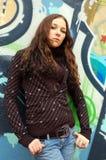 Ragazza vicino alla parete dei graffiti Immagine Stock