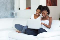 Ragazze afroamericane dello studente che per mezzo di un computer portatile - p nera Fotografia Stock Libera da Diritti