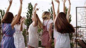 Ragazze alla moda sull'addio al nubilato fuori sul terrazzo Getti i coriandoli d'argento nell'aria Lo stile di vita felice, gode  video d archivio