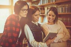 Ragazze allegre degli studenti in biblioteca che leggono insieme libro Immagini Stock Libere da Diritti