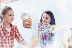 Ragazze astute emozionanti che mescolano i liquidi durante la lezione di chimica alla scuola Fotografie Stock