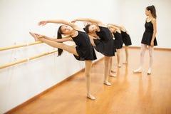 Ragazze che allungano durante la classe reale di balletto immagine stock