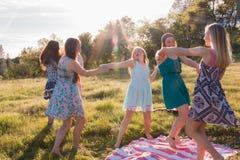 Ragazze che ballano nel campo erboso con luce solare al di sopra Fotografie Stock