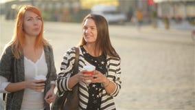 Ragazze che camminano intorno alla città su un caffè della bevanda e di giorno soleggiato video d archivio