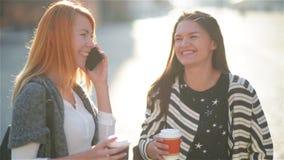 Ragazze che camminano intorno alla città un giorno soleggiato con i telefoni ed il caffè della bevanda video d archivio