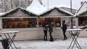 Ragazze che comprano le ciambelle dal venditore giusto della città di natale Caduta della neve archivi video