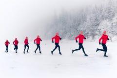 Ragazze che corrono insieme sulla neve in montagne di inverno Sport, ispirazione di forma fisica e motivazione  immagine stock