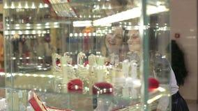 Ragazze che esaminano vetrina in una gioielleria video d archivio