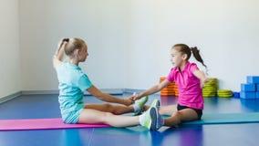 Ragazze che fanno gli esercizi relativi alla ginnastica o che si esercitano nella classe di forma fisica video d archivio