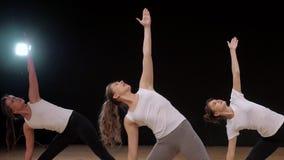 Ragazze che fanno yoga, gruppo di persone in una classe d'allungamento, stile di vita sano archivi video