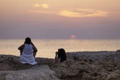 Ragazze che fotografano un tramonto dorato Immagini Stock