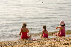 Ragazze che gettano pietra nel mare Fotografie Stock Libere da Diritti
