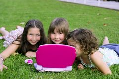 Ragazze che giocano con il calcolatore del giocattolo in erba Fotografie Stock Libere da Diritti