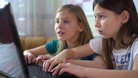 Ragazze che giocano i giochi di computer sul computer portatile archivi video