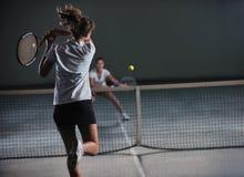 Ragazze che giocano il gioco di tennis dell'interno Immagini Stock