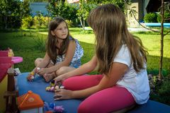 Ragazze che giocano le bambole del whith di estate immagine stock libera da diritti