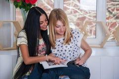 Ragazze che guardano insieme e che discutono leggendo rivista fotografia stock
