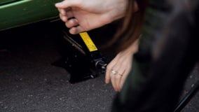 Ragazze che il lato della strada impara cambiare il pneumatico sul suo primo piano dell'automobile stock footage