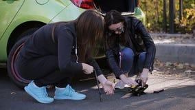 Ragazze che il lato della strada impara cambiare il pneumatico sulla sua automobile stock footage