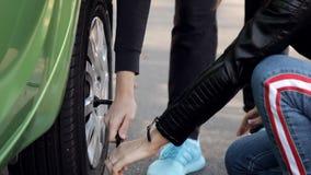 Ragazze che il lato della strada impara cambiare il pneumatico sulla sua automobile video d archivio