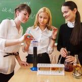 Ragazze che lavorano nel laboratorio di chimica all'aula Immagini Stock
