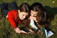 Ragazze che leggono i libri sul prato inglese Fotografia Stock