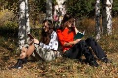 Ragazze che leggono nella sosta Fotografia Stock