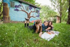 Ragazze che leggono un libro nel parco Immagine Stock