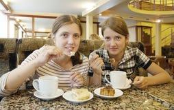 Ragazze che mangiano una pasticceria del biscotto al coffee-room immagine stock