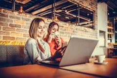 Ragazze che per mezzo del computer portatile e bevendo caffè Immagini Stock