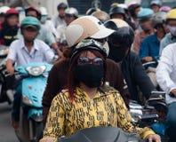 Ragazze che portano la maschera di protezione in Saigon inquinante Fotografie Stock