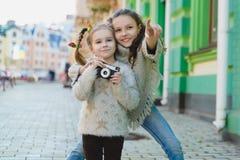 Ragazze che posano e che fotografano su una retro macchina fotografica nella città fotografia stock