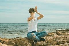 Ragazze che praticano le pose di yoga sulla spiaggia Stile di vita sano immagini stock