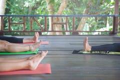 Ragazze che praticano yoga all'aperto durante la vacanza della ritirata di yoga Ritirata di lusso di yoga fotografia stock