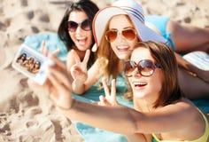Ragazze che prendono la foto di auto sulla spiaggia Fotografia Stock