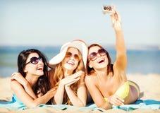 Ragazze che prendono la foto di auto sulla spiaggia Fotografie Stock Libere da Diritti