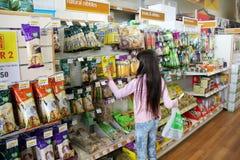 Ragazze che scelgono i prodotti dell'animale domestico Immagine Stock