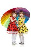 Ragazze che si levano in piedi sotto l'ombrello variopinto Immagine Stock