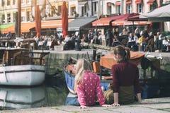 Ragazze che si siedono sulla citt? francese famosa Honfleur del fondo fotografia stock libera da diritti