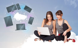 Ragazze che si siedono sulla nuvola che gode del servizio in rete della nuvola Fotografie Stock
