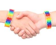 Ragazze che stringono le mani con un braccialetto modellato come la bandiera dell'arcobaleno Su bianco Fotografie Stock