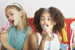 Ragazze che usando le spazzole come microfoni al pigiama party immagini stock